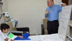 Öğretmen, öğrencisine hastane odasında ders veriyor
